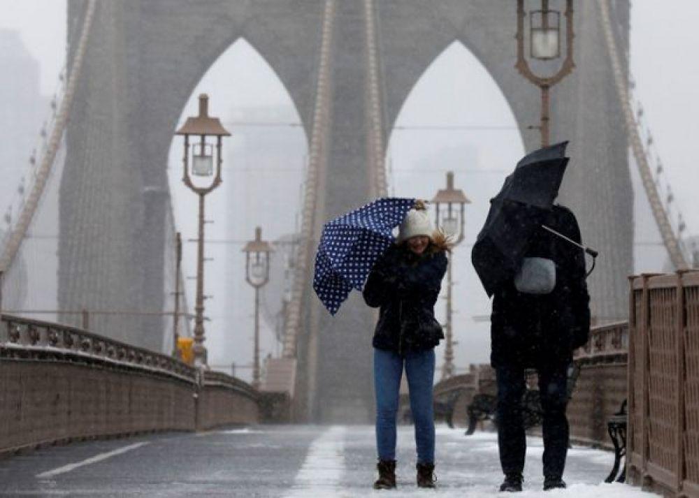 Люди борются с ветром и снегом на Бруклинскому мосту в Нью-Йорке.