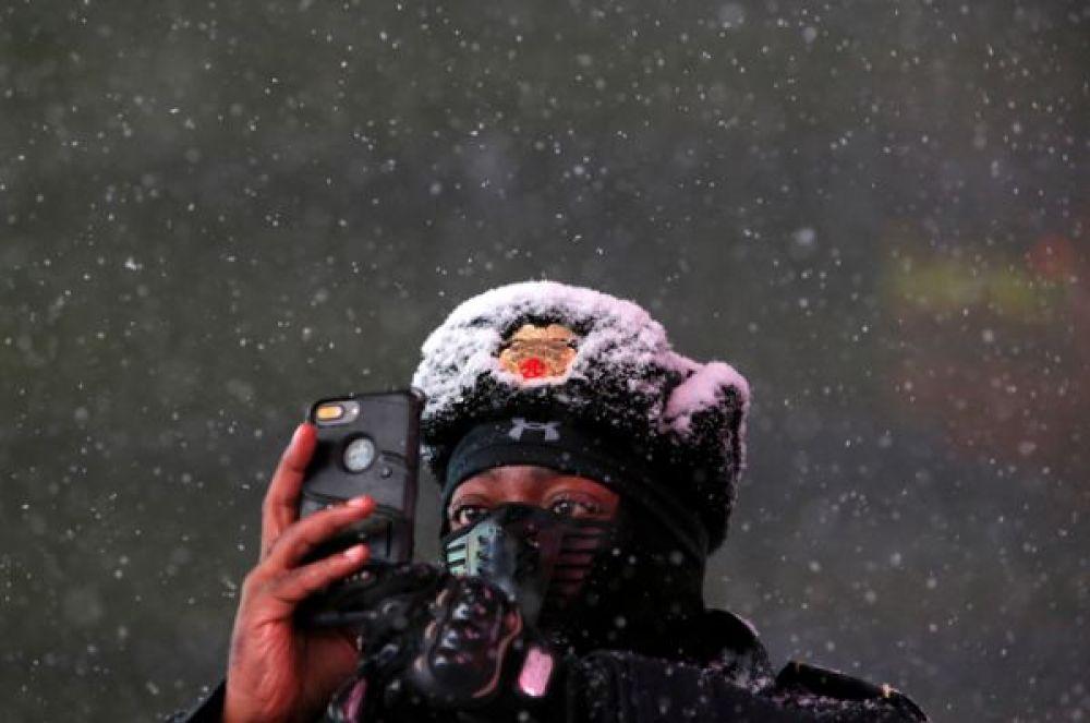Сержант полиции Болдуин Дэвис фотографирует падающий снег на свой мобильный телефон, Манхэттен, Нью-Йорк.