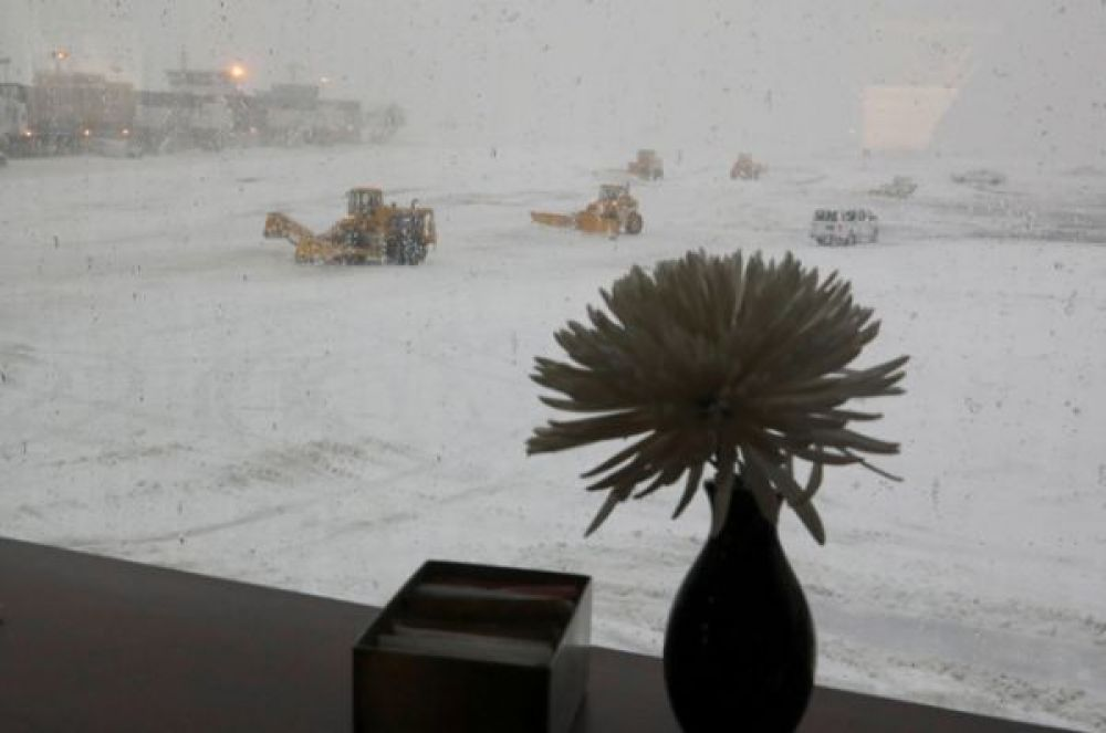 Снегоочистители очищают взлетно-посадочную полосу в аэропорту Ла-Гуардия в Нью-Йорке.