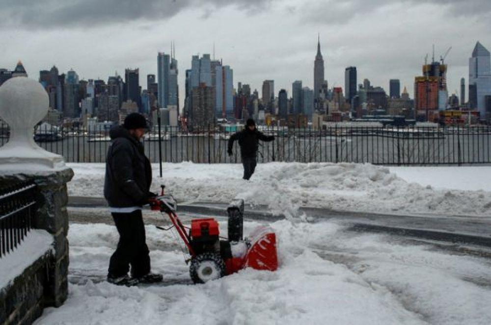 Житель очищает улицу после метели в Нью-Джерси. На заднем плане видны Эмпайр-стейт-билдинг и Средний Манхэттен.