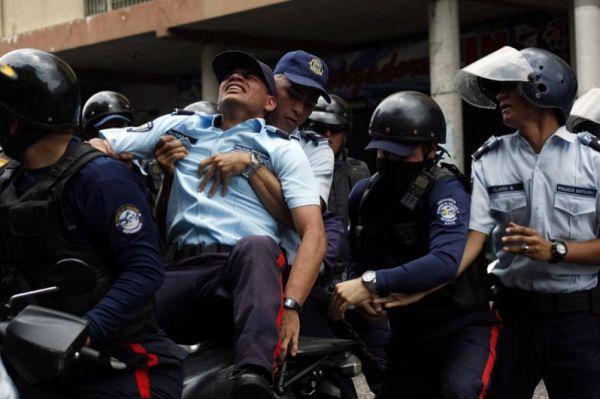 Раненый полицейский во время столкновений с оппозицонерами во время протестов против президента Николаса Мадуро в Сан-Кристобаль.