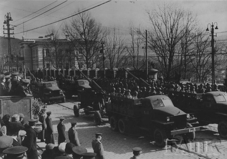 Колонна артиллерии двигается по празднующей улице.