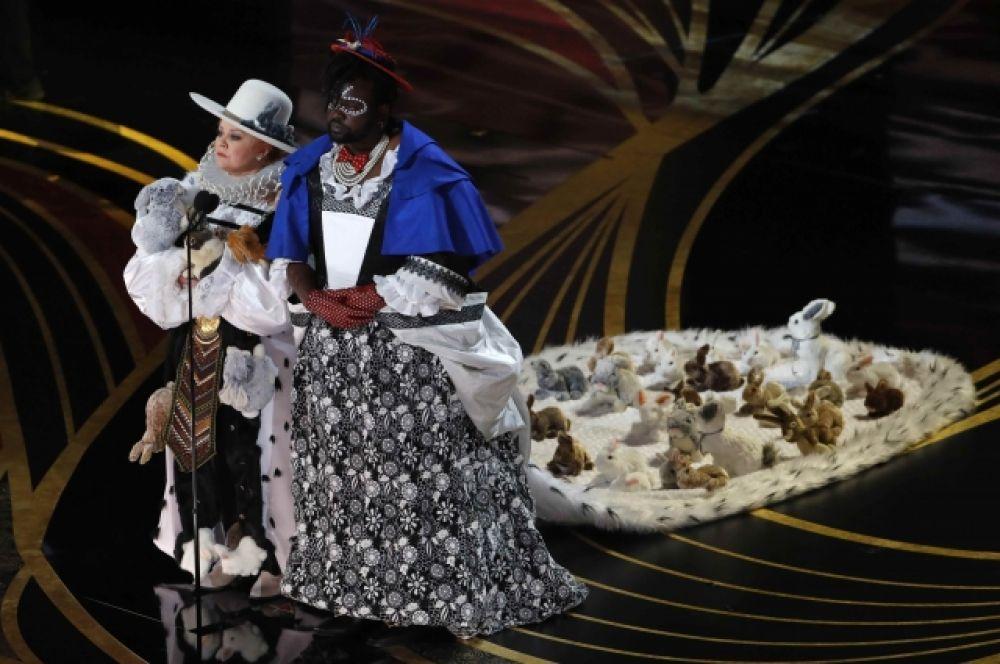 На сцене Мелисса МакКарти и Брайан Терри Хенри, в костюмах, навеянных «Алисой в стране чудес». Они вручили премию за лучший костюм.