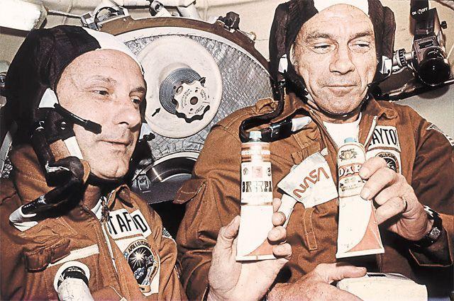 Американские астронавты Том Стаффорд и Дик Слейтон держат тюбики с «русской водкой», которую им дал Алексей Леонов в совместном полёте «Союз» – «Аполлон» в 1975 г.