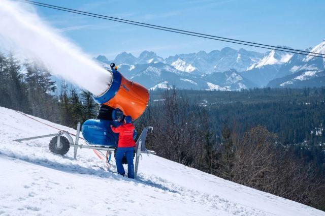 Гигантские вентиляторы распыляют воду, которая на морозе превращается в снег.