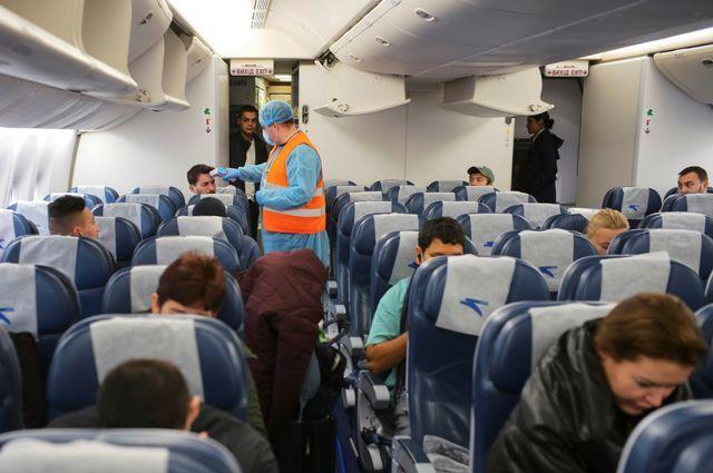 Медицинский работник с защитным снаряжением ходит в самолете, измеряя температуру тела пассажиров, прибывших рейсом из Нью-Йорка, в качестве меры предосторожности против коронавируса (COVID-19) в международном аэропорту Борисполь под Киевом, Украина.