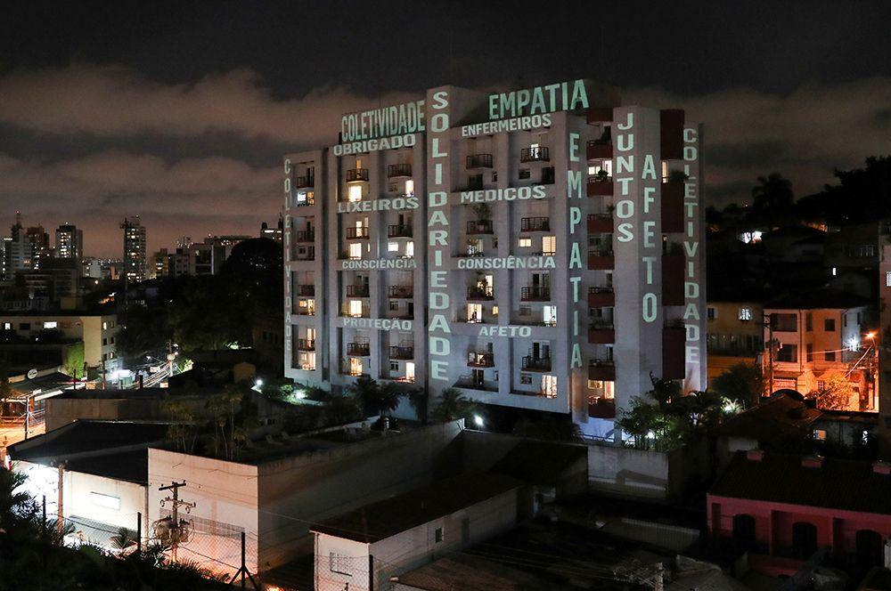 Слова «солидарность», «сопереживание», «привязанность» и фраза «спасибо, врачи, медсестры, сборщики мусора» на здании в Сан-Паулу, Бразилия.