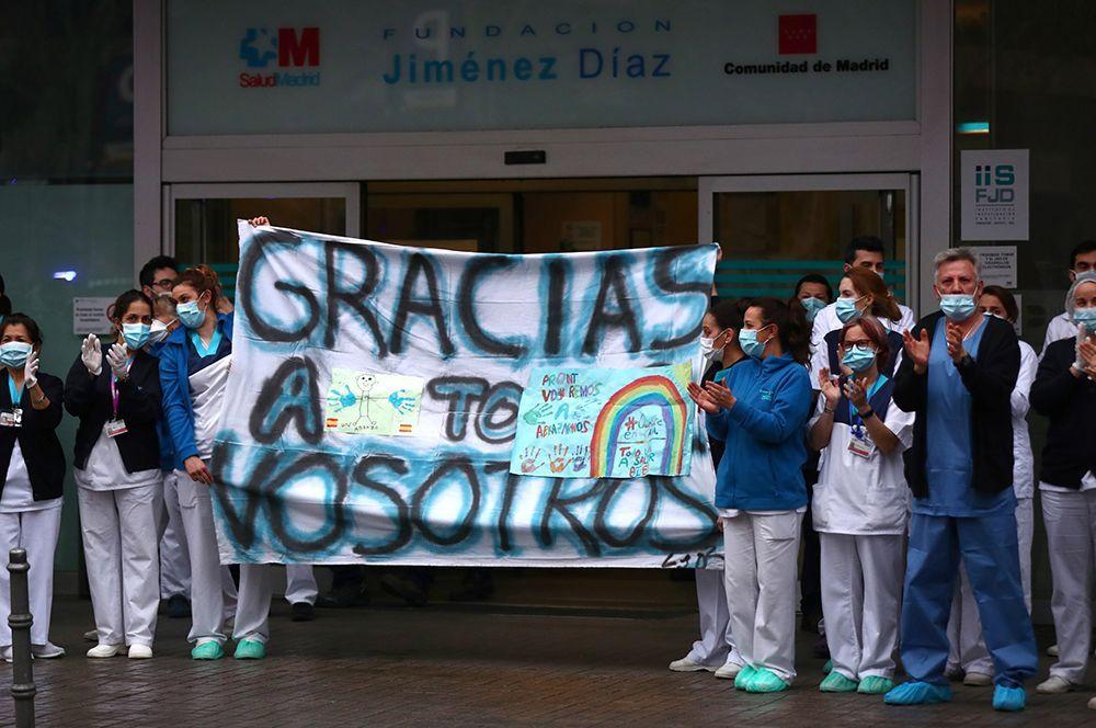 Работники больницы Fundacion Jimenez Diaz держат плакат с надписью «Спасибо всем», в то время как люди аплодируют им со своих балконов, Мадрид, Испания.