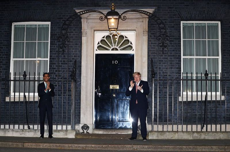Премьер-министр Великобритании Борис Джонсон и канцлер казначейства Риши Сунак аплодируют медикам на Даунинг-стрит, 10, Лондон.