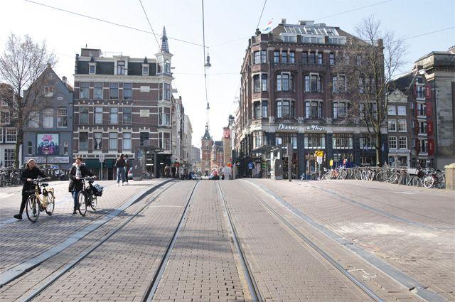 Жители Амстердама соблюдают дистанцию 1,5 м на практически пустых улицах.