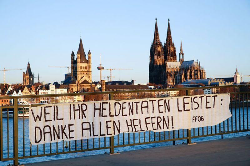 Плакат с надписью: «Потому что вы совершаете героические поступки, спасибо всем, кто помогает» на мосту перед Кельнским собором, Кельн, Германия.