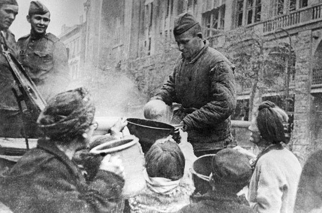 Повсюду в Берлине развернуты советские полевые кухни, у которых кормят голодных горожан. Май 1945 г.