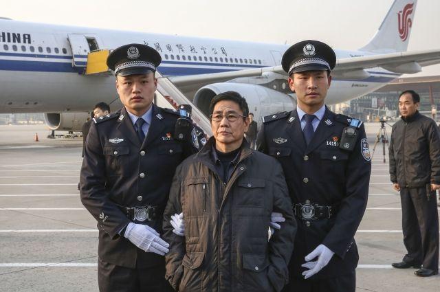 Полиция сопровождает Яо Цзиньци в Пекине. Яо Цзиньци — подозреваемый в совершении преступления бывший заместитель главы округа Синьчан на востоке Китая. Его экстрадировали из Болгарии. Яо, бежавший за границу в декабре 2005 года, стал первым бывшим государственным служащим, которого Китай экстрадировал из страны-члена ЕС. 2018 г